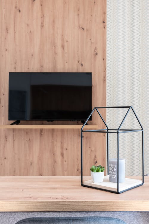 House interior with table with small decorative objects near TV on wooden wall