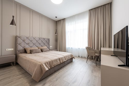 Bedroom interior with bed near table with TV
