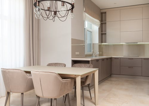 Kitchen interior with chairs and table near cupboards