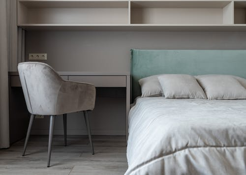 Apartment interior with bed near table with chair