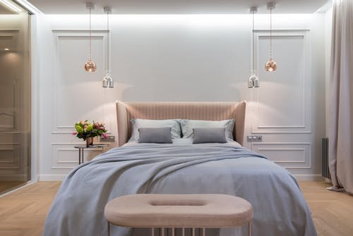Bedroom interior with bed near table under lamps
