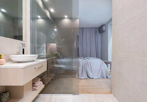 Interior of light modern restroom with sink and faucet on cabinet under mirror on wall next to glass door to bedroom with bed