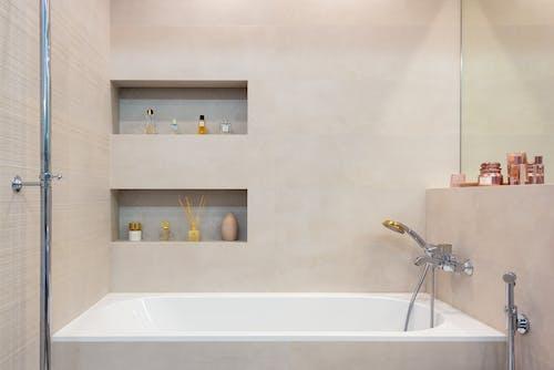 Bathroom interior with bathtub with shower under shelves