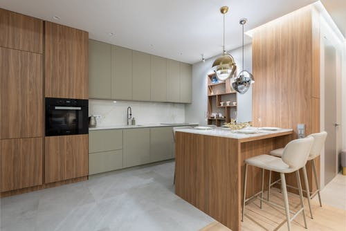 Interior of bright modern kitchen with cupboards near chairs with counter decorated with glasses and plates under lamps next to shelves on wall
