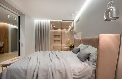 Interior of modern light bedroom with pillows and blanket on bed under lamps next to pouf near glass wall with curtain