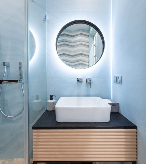 Interior of modern bright restroom with sink and tap on counter under round mirror on wall next to glass wall to shower