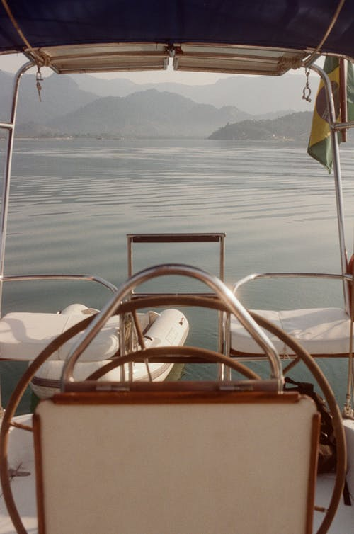 Yacht with boat sailing on rippling water of pond surrounded by hills in haze