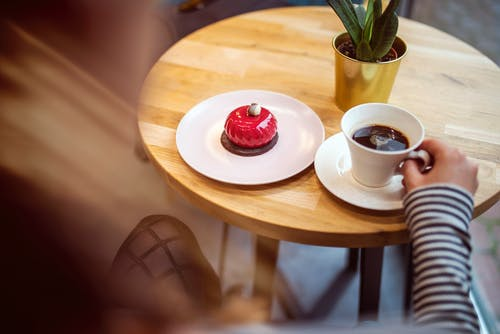 From above of crop anonymous lady in casual outfit drinking aromatic coffee and eating yummy glaze cake while sitting at round wooden table in modern cafe