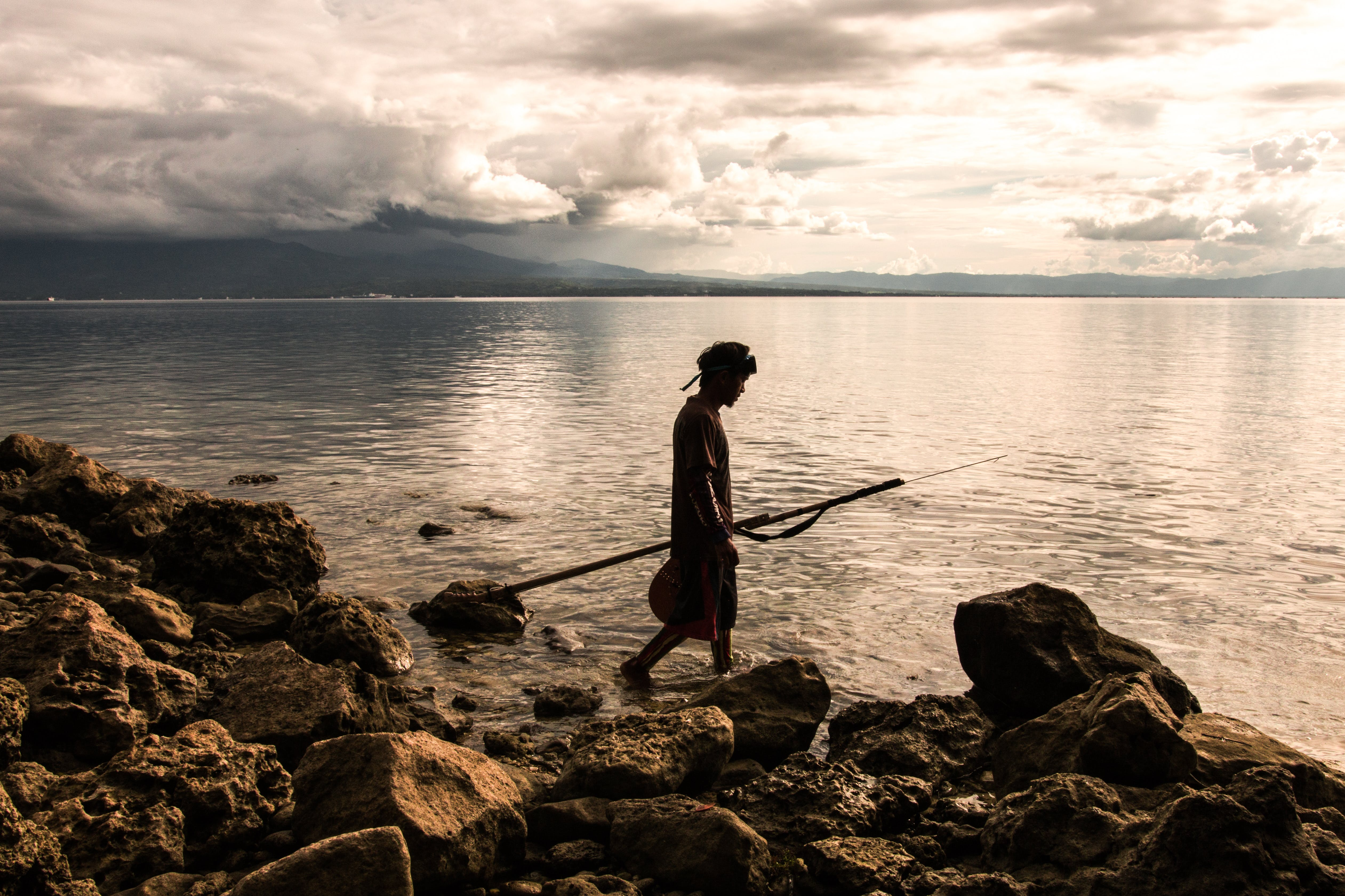 Person Holding Spear Beside Body of Water