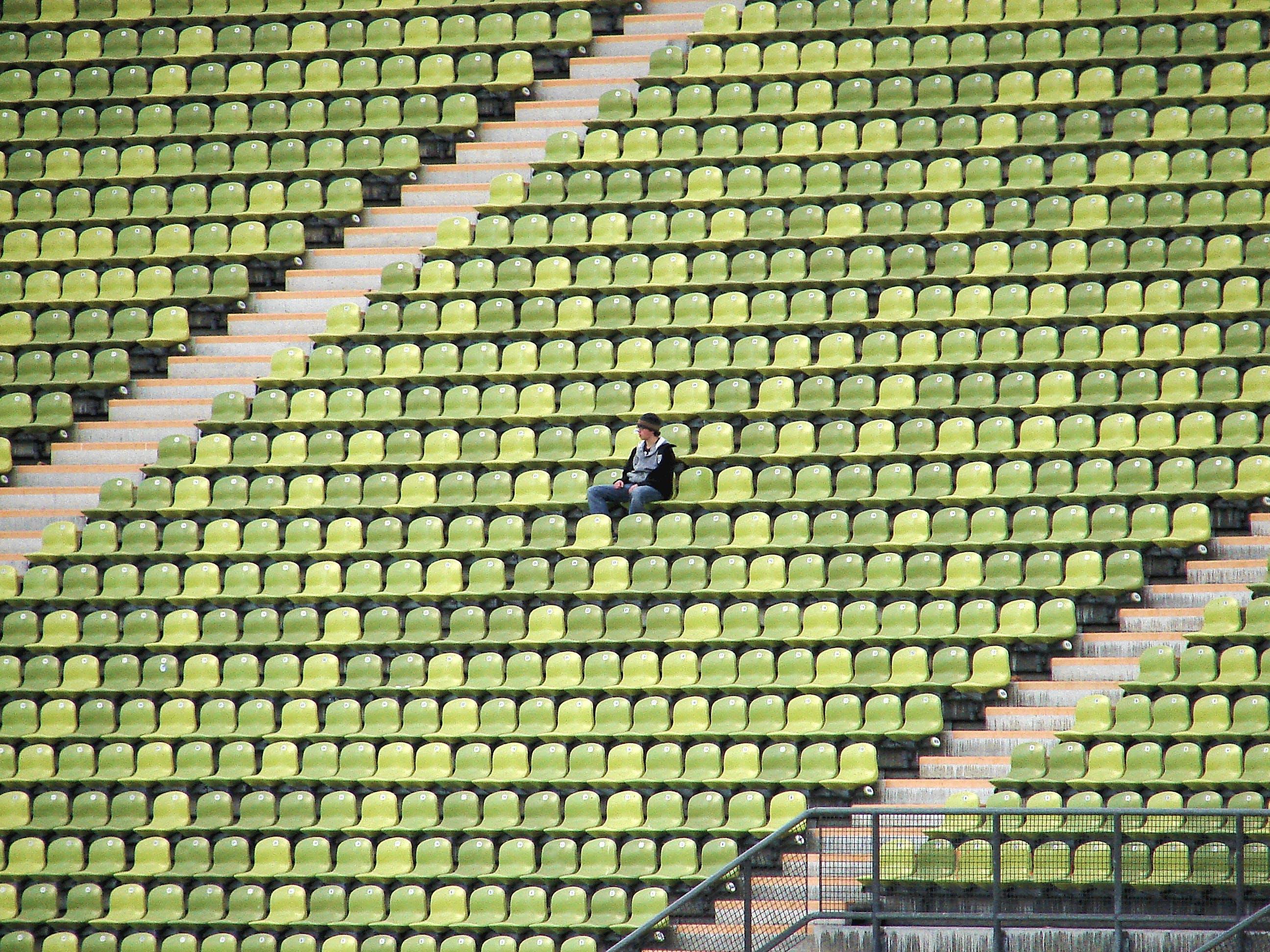 Woman in Grey Shirt Sitting on Stadium Chair