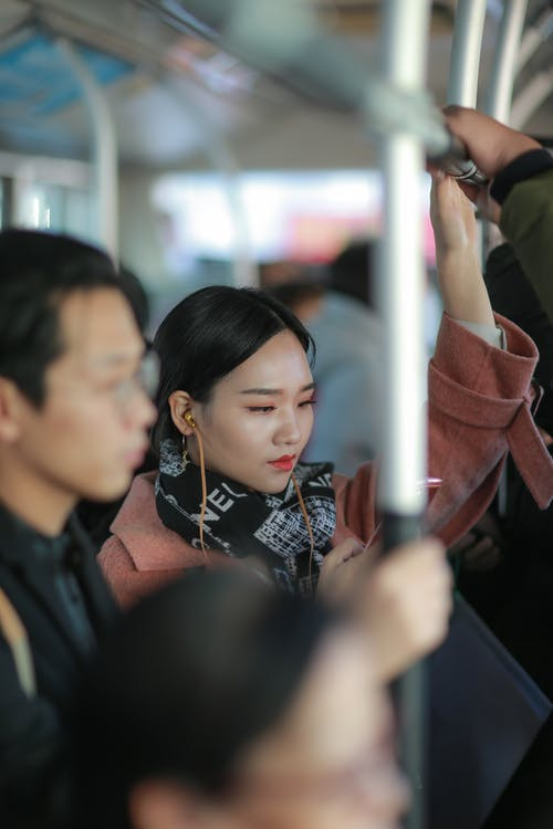 Stylish young Asian female passenger in stylish outfit and earphones standing in crowded public transport and holding metal handrail