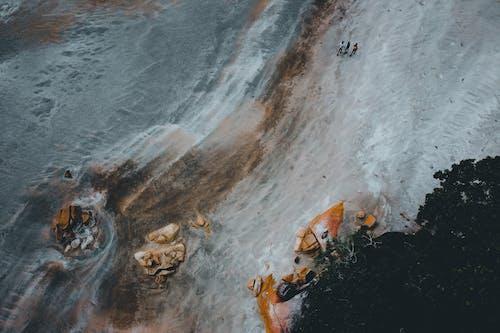 Anonymous people walking on sandy seashore near rocky boulders