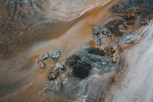 Rough stones scattered on ocean sandy beach