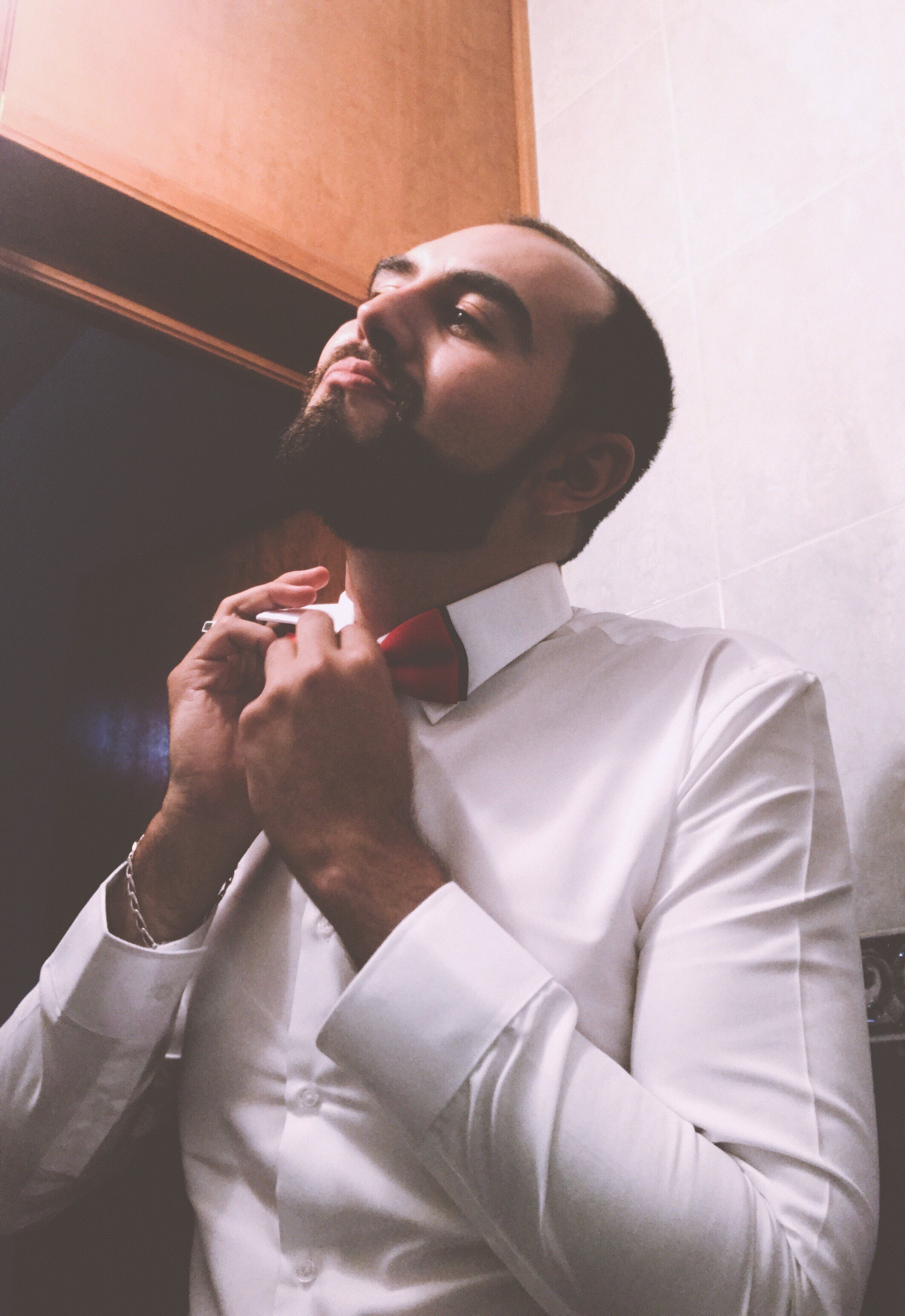 Man in White Dress Shirt Tying a Red Bow Tie