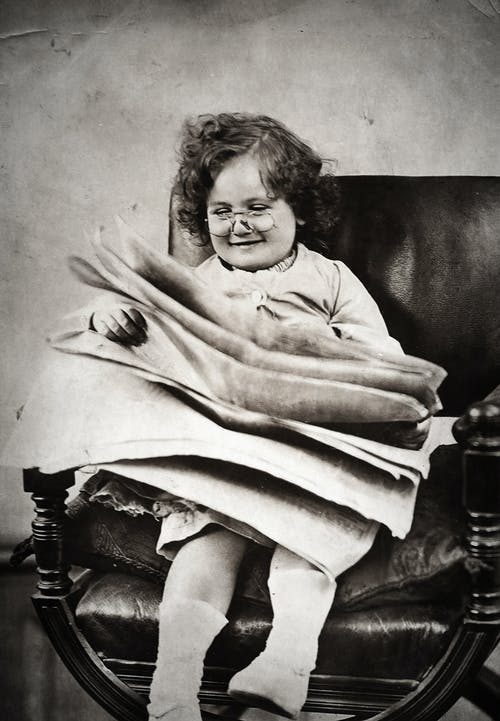 Little Girl With Eyeglasses Smiling While Reading Newspaper