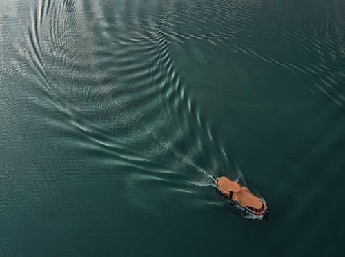 Drone view of brown vessel sailing on calm dark green ocean and leaving mark on water surface