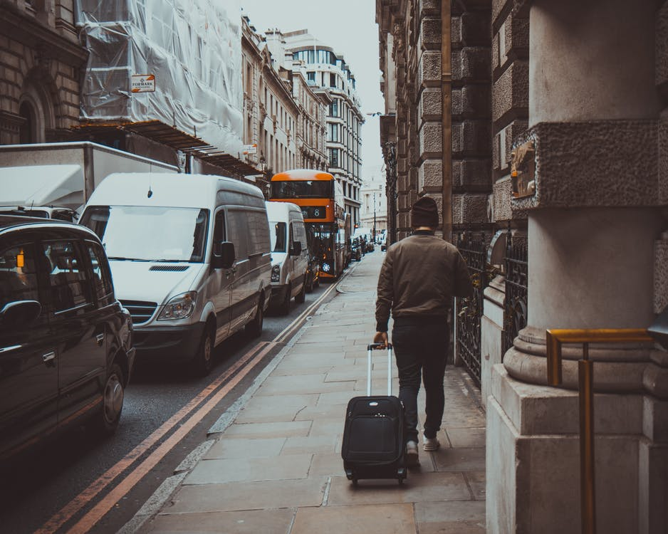 Man in Brown Jacket Holding Black Travel Luggage