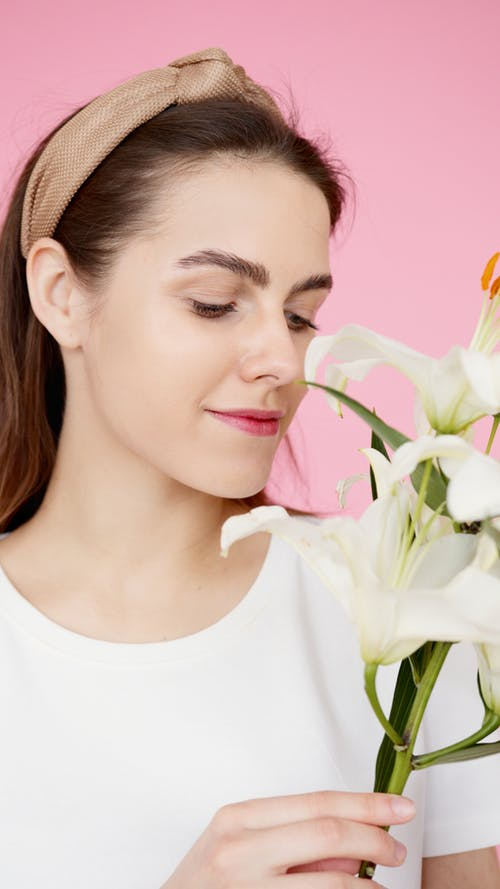 Woman In White T Shirt With Headband Holding White Flowers