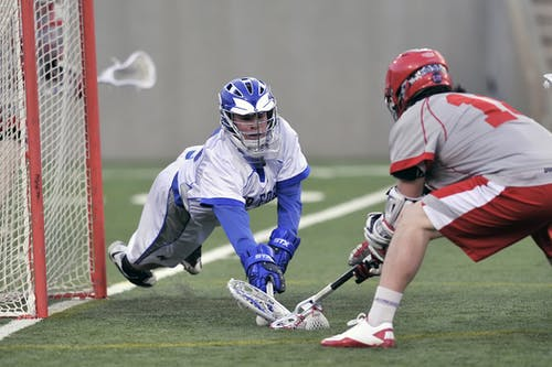 Person Wearing Blue Gloves Holding Lacrosse Stick