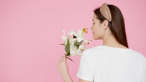 Photo of Woman Holding White Flowers With Pink Background