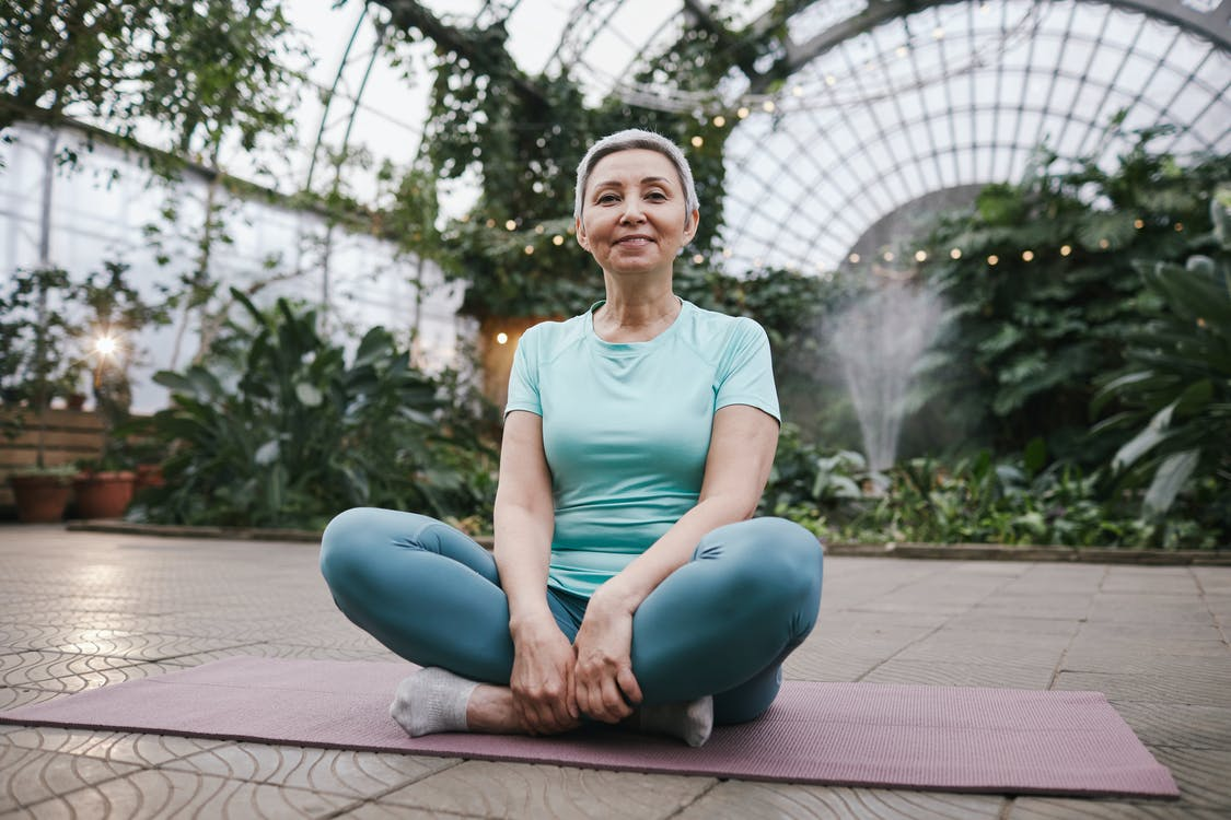 Woman Sitting on a Yoga Mat While Smiling
