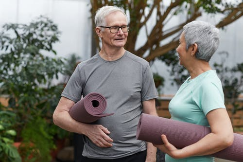 Couple Holding Yoga Mats While Looking at Each Other