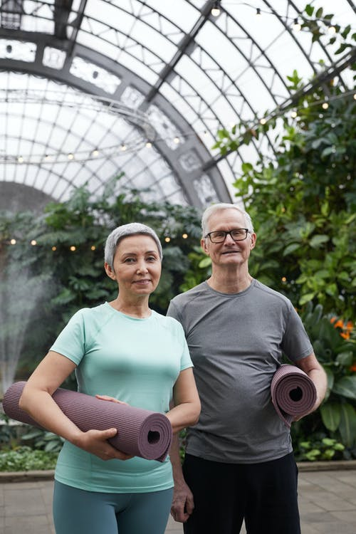 Couple Smiling While Holding Yoga Mats