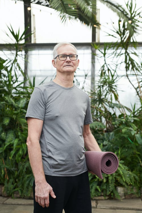 Man Standing While Holding a Yoga Mat