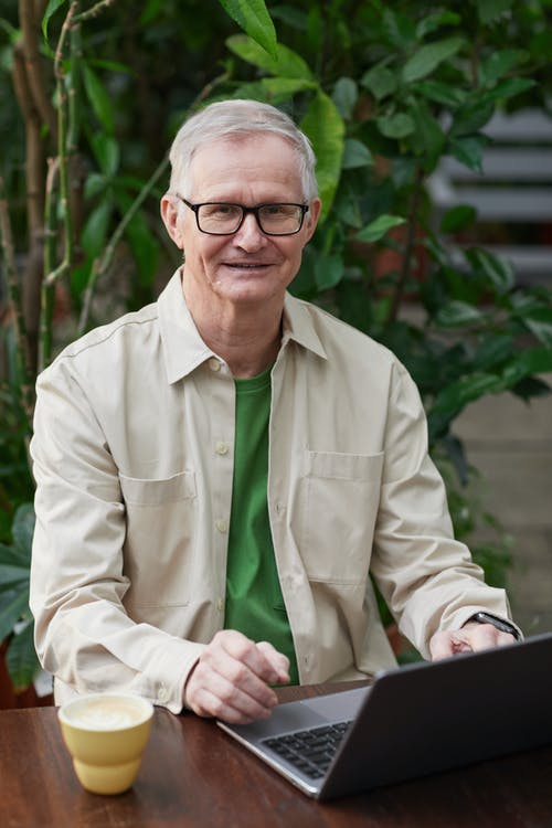 Man Smiling While Using His Laptop