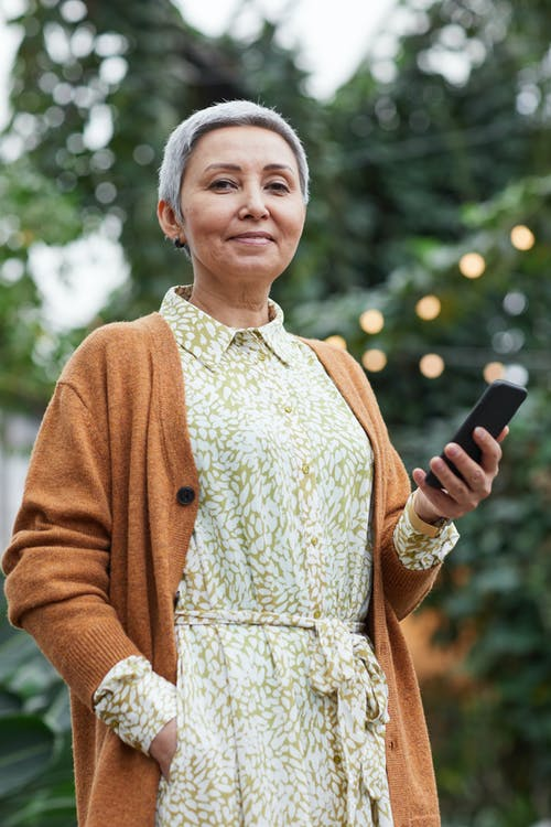 Woman Holding Her Smartphone While Smiling at the Camera