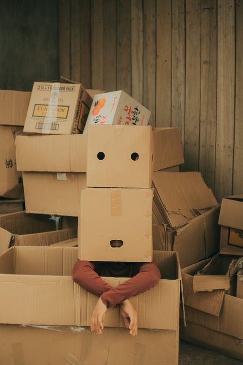 Faceless person sitting in big box with carton box on head wearing casual clothes near wall in light place