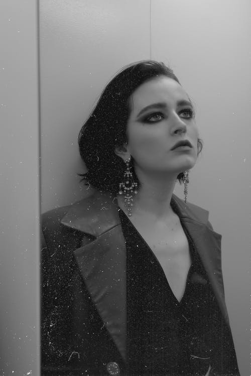 Black and white of eccentric female in elegant clothes with large earrings looking up