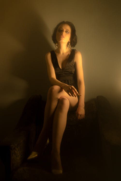 Full body of slender female with short dark hair in black gown looking at camera