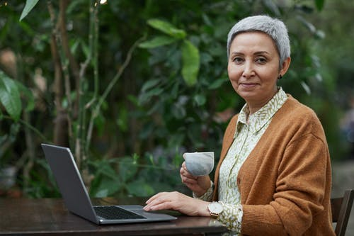 Woman Using Her Laptop While Holding a Coffee Cup
