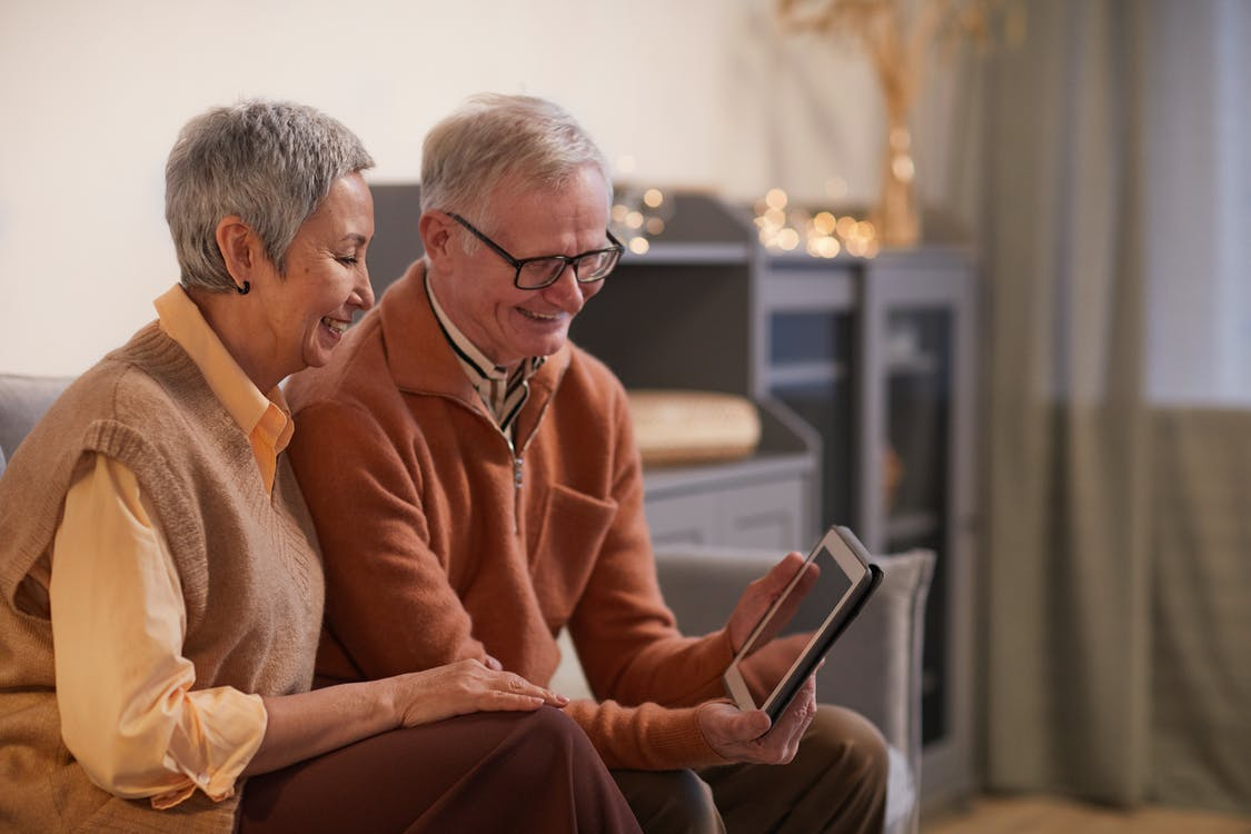 Couple Smiling While Looking at a Tablet Computer