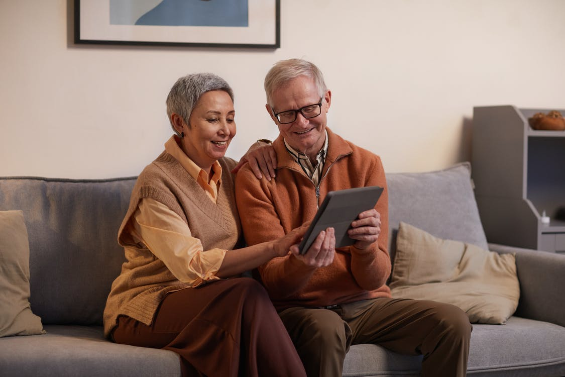 Man and Woman Sitting on Sofa While Looking at a Tablet Computer