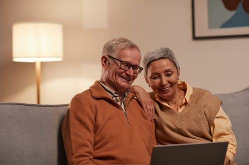 Man and Woman Sitting on Sofa While Looking at a Laptop
