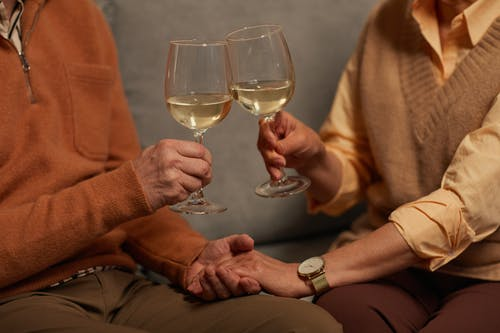 Couple Holding Each Other's Hands While Holding a Wine Glasses