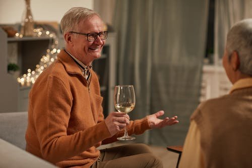 Man in Brown Sweater Smiling While Holding Wine Glass
