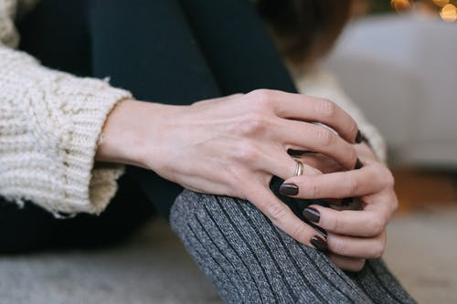 Person in Gray Sweater Holding Black Textile