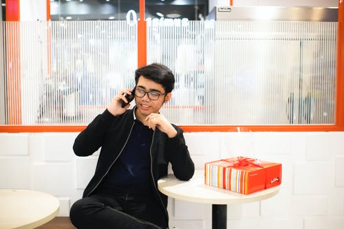 Asian man speaking on smartphone near table with gift box