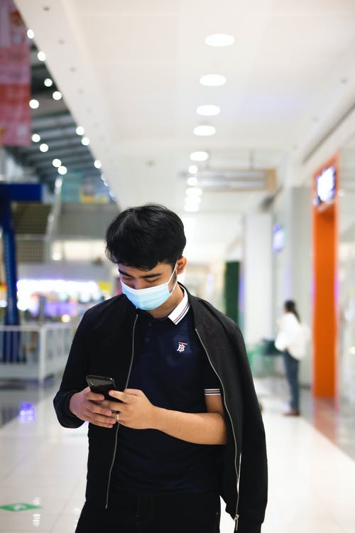 Young man in casual clothes and mask surfing on smartphone while standing in light mall