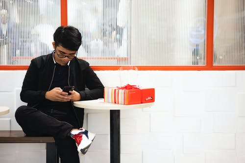 Man using cellphone near table with gift box in cafe