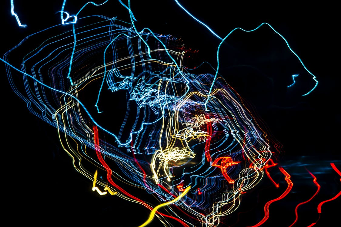 Abstract backdrop of glowing vivid freezelights making shimmering colorful lines in dark night