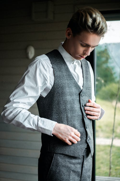 Elegant young businessman in formal outfit standing in house