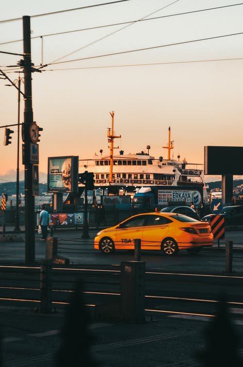 Contemporary cab on roadway against ship under light sky in urban port at sundown