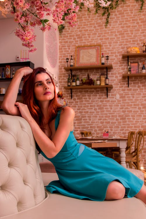Woman in Teal Sleeveless Dress Sitting on White Couch