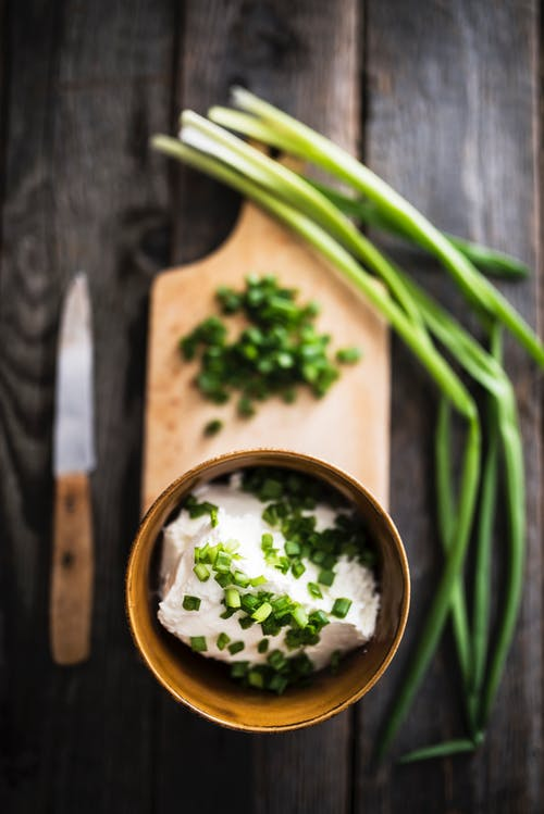 Sour cream with green onion placed on wooden cutting board
