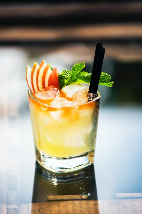 Glass of cold citrus cocktail with fresh mint and pieces of apple placed on table in daytime