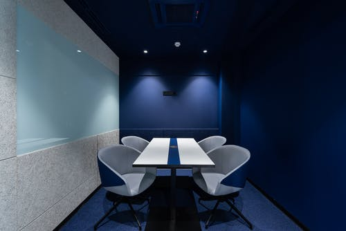 Comfortable chairs placed on carpet at long white desk in modern conference room with blue walls in contemporary business center